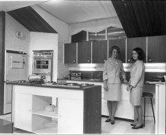 RDS home exhibit, kitchen with demonstrators, 1960s