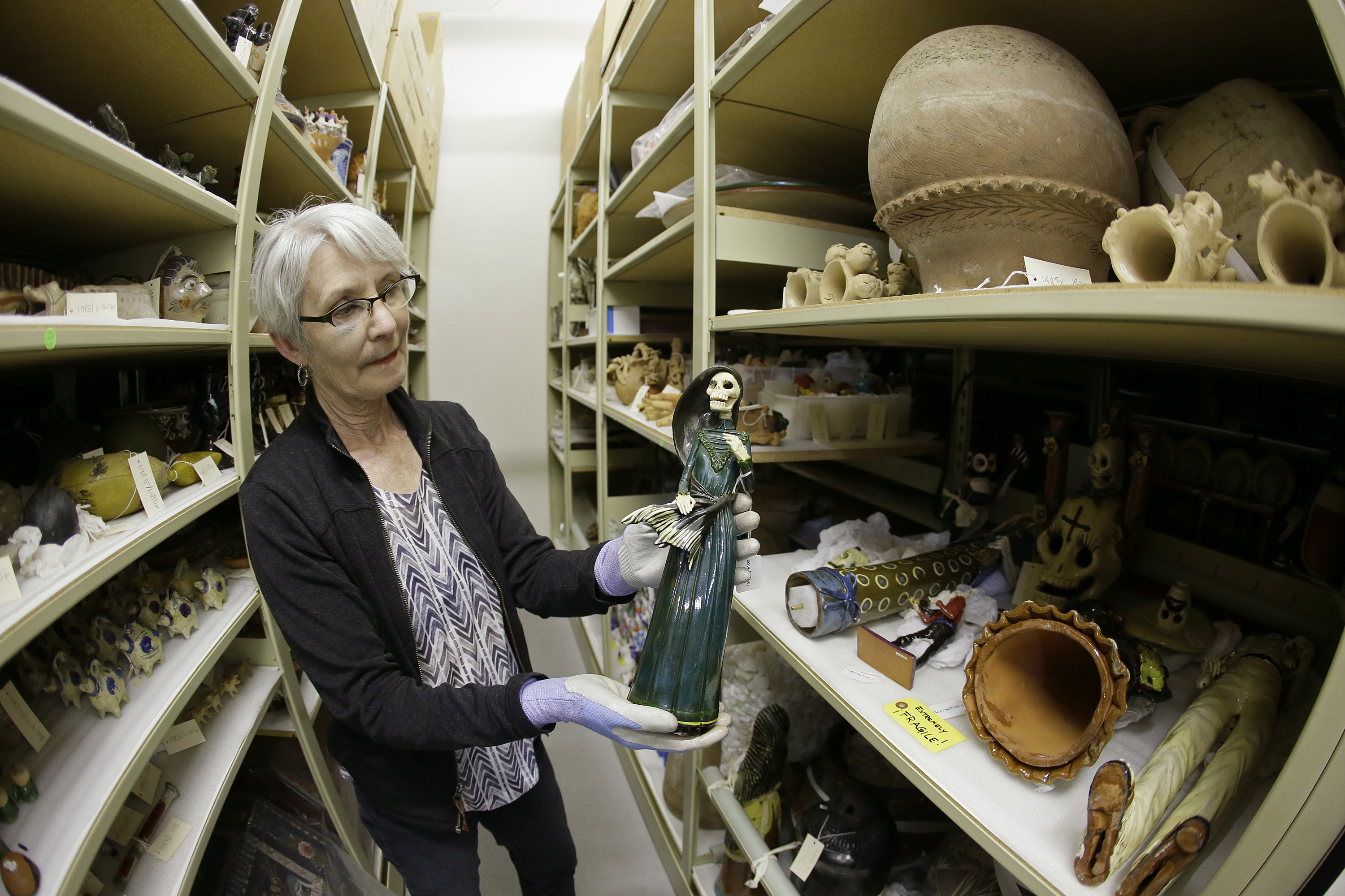 """In this photo taken Monday, June 27, 2016, registrar Wendy Niles holds a Day of the Dead sculpture """"La Soldadera"""" by Alvaro de la Cruz being stored in a vault at the Mexican Museum currently located at Fort Mason in San Francisco. Construction of a four-story, state-of-the-art Mexican Museum is underway, realizing the dream of a late Mexican-American artist who four decades ago opened the city's first museum for Latino art in a Mission District storefront. The 60-000 square feet building in downtown San Francisco will be home to 16,000 pre-Columbian, colonial, modern and contemporary works of Mexican, Mexican-American and Latino art, the largest such collection in the country. (AP Photo/Eric Risberg)"""