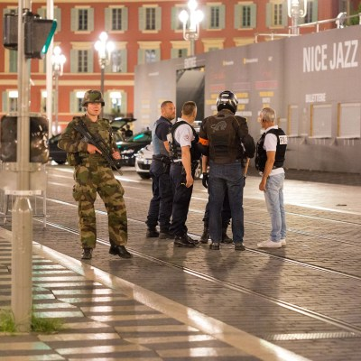 Police officers and a soldier stand by the sealed off area of an attack after a truck drove on to the sidewalk and plowed through a crowd of revelers who'd gathered to watch the fireworks in the French resort city of Nice, southern France, Friday, July 15, 2016. A spokesman for France's Interior Ministry says there are likely to be