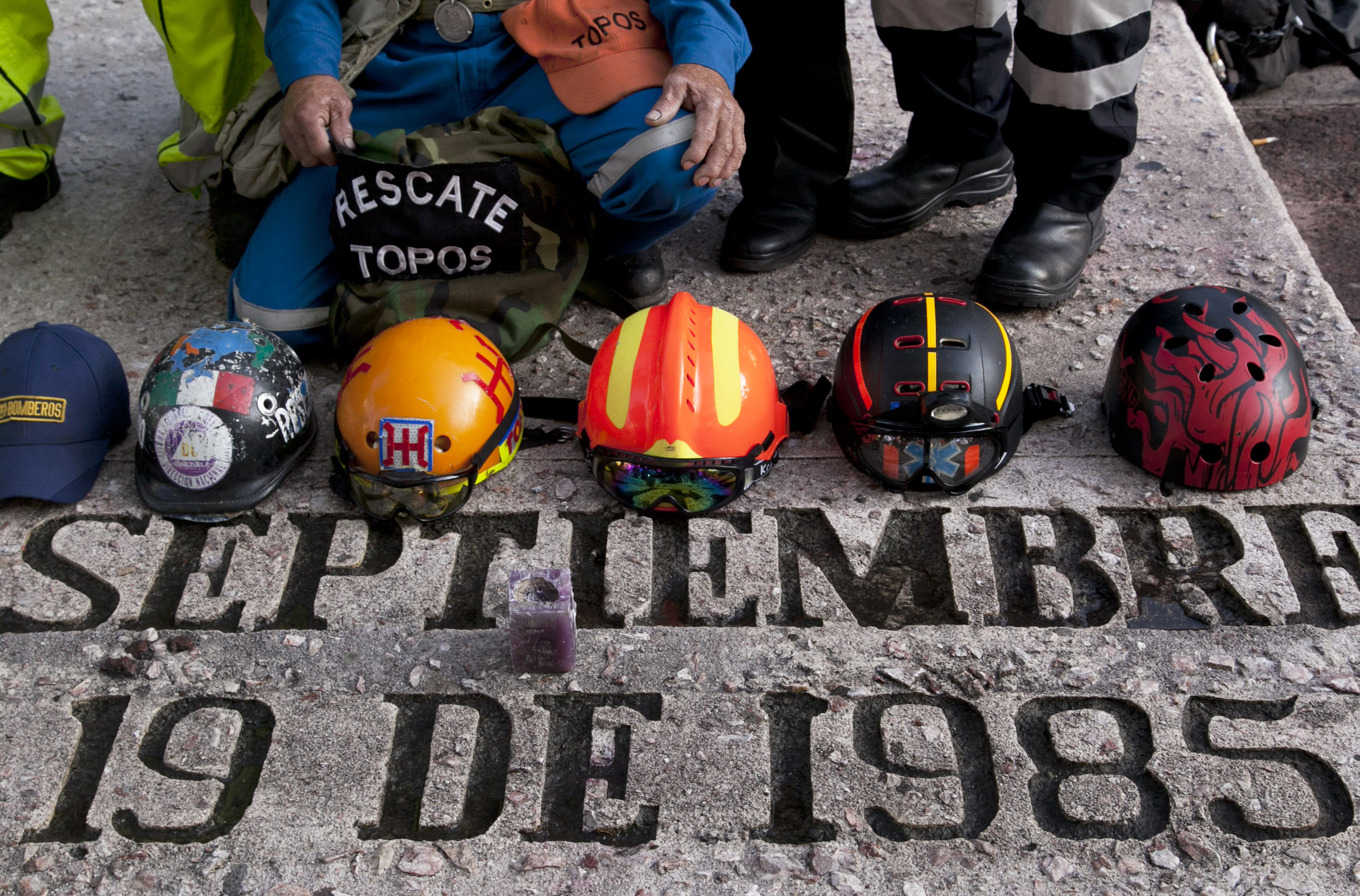 Rescue workers' hats sit on a memorial honoring those who died in the 1985 earthquake on the 30th anniversary in Mexico City, Saturday, Sept. 19, 2015. Voluntary civil brigades were created to lead rescue operations after the 8.1-magnitude earthquake struck Mexico City, killing thousands of people and leaving many homeless. (AP Photo/Marco Ugarte)