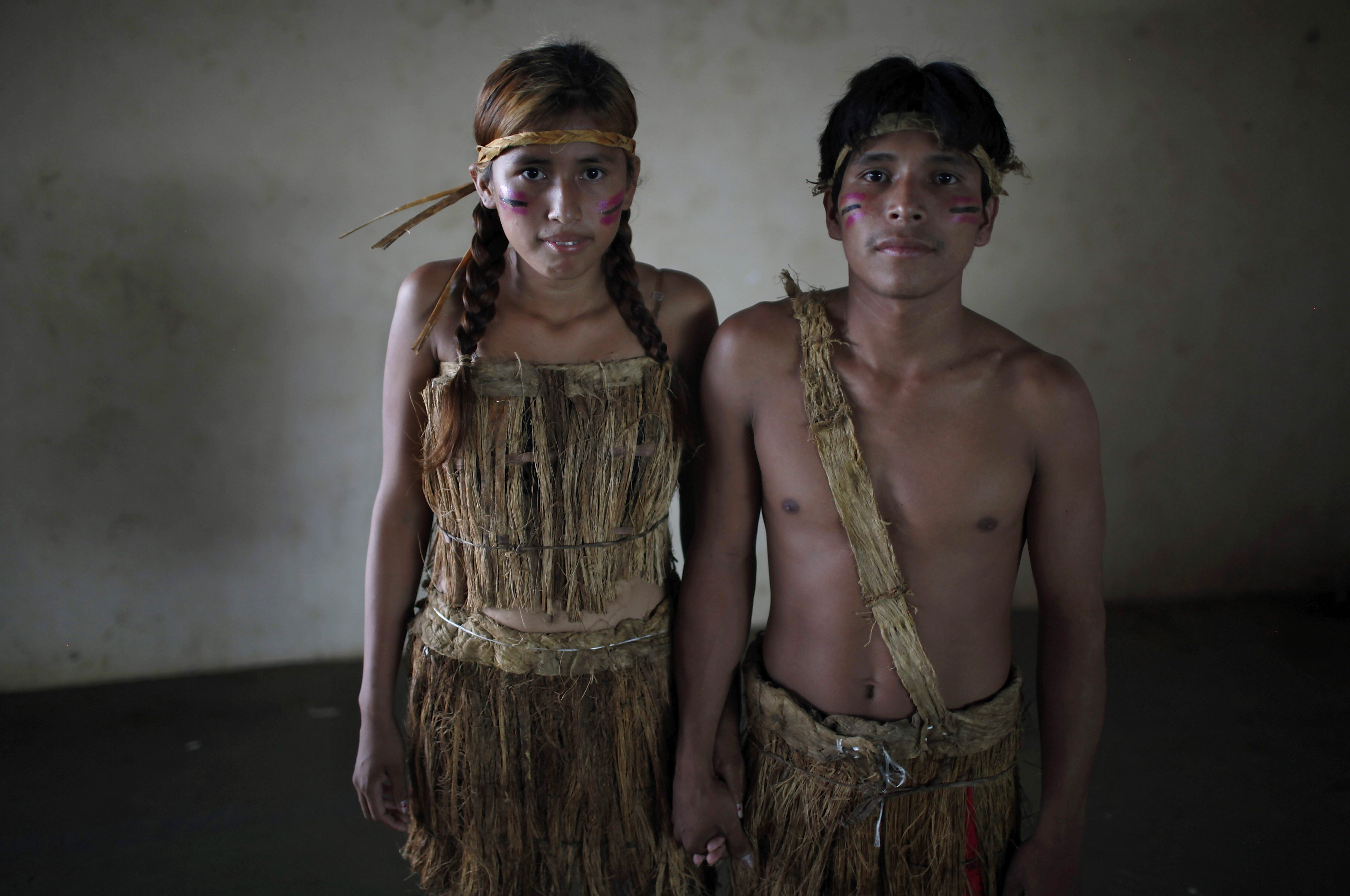 "Erika Kanacmi, left, and Denis Capi, an Esse Ejja indigenous couple, pose for a portrait before a collective wedding ceremony in Cobija, Bolivia, Saturday, Oct. 6, 2012. Indigenous couples from Bolivia's Amazon region got married in a mass wedding coined ""Collective Marriage from our Identity 2012,"" organized by the government. Many of the couples were already legally married, but wanted to attend a ceremony that included some indigenous traditions from the Amazon. (AP Photo/Juan Karita)"