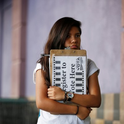 Fabiola Vejar waits to register people to vote in front of a Latino supermarket in Las Vegas on Thursday, June 9, 2016. Shielded from deportation under an Obama administration program that protects those brought to the country illegally as children, Vejar, 18, cannot vote. So she volunteers with Mi Familia Vota, encouraging others to be heard at the ballot box.
