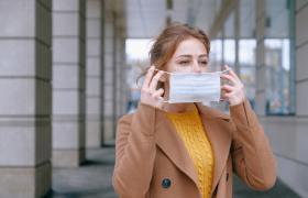 mulher colocando uma máscara em seu rosto