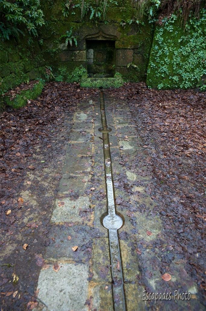 A flanc de la paroi granitique, la fontaine de la chapelle N-D de La Fosse recueille les eaux d'une source aux eaux claires