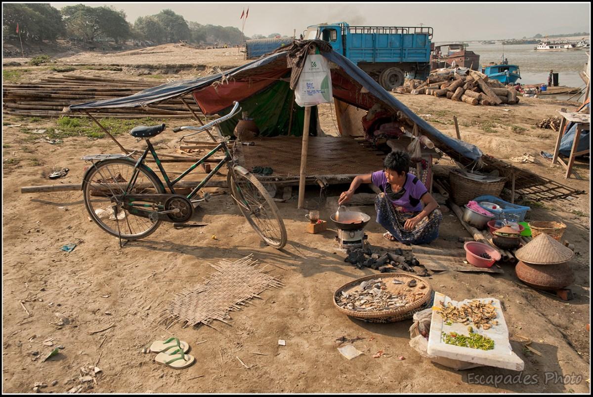 La vie quotidienne sur les berges de l'Irrawaddy - une cabane sommaire, un vélo, quelques ustensiles de cuisine et une femme préparant un repas.