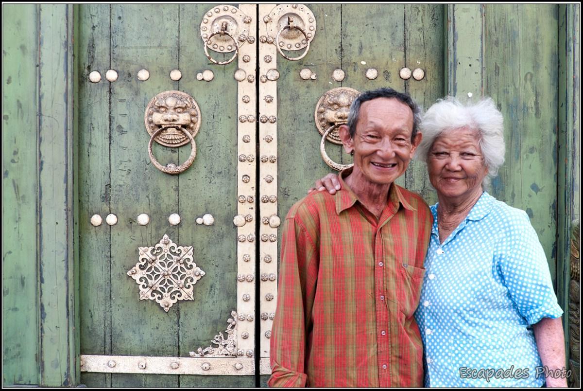 Couple de malais devant une maison chinoise
