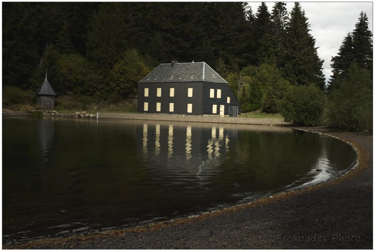 Maison noire à volets jaunes au lac de Montcineyre