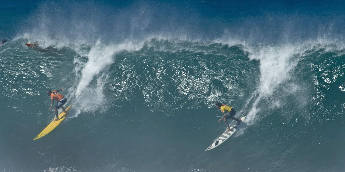 Sunny Garcia, left and Greg Long, right, drop into one of their heat's last waves at the Quiksilver In Memory of Eddie Aikau big wave surf contest on the North Shore at Waimea Bay, Hawaii Tuesday. ///ADDITIONAL INFO:01.eddieNEW.p120809.mg - 12/08/09 - Photo by MICHAEL GOULDING,THE ORANGE COUNTY REGISTER - Additional info, CQs, and keywords for searching. Generic Caption: the Quiksilver In Memory of Eddie Aikau big wave surf contest on the North Shore at Waimea Bay, Hawaii Tuesday.