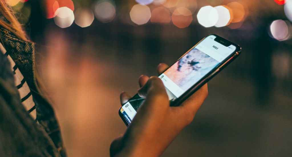 apps de viaje sujetando telefono movil