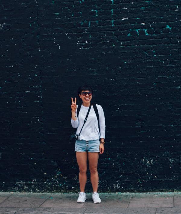 chica viajera posando en pared oscura