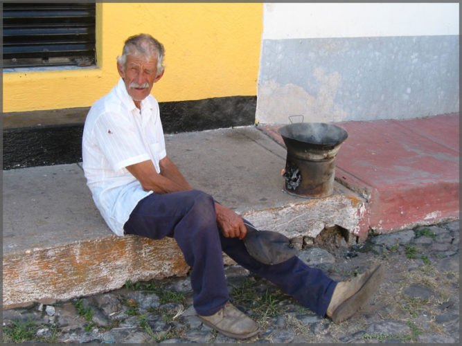 Man using a primitive wood stove to cook on the street in Ajijic, Mexico.