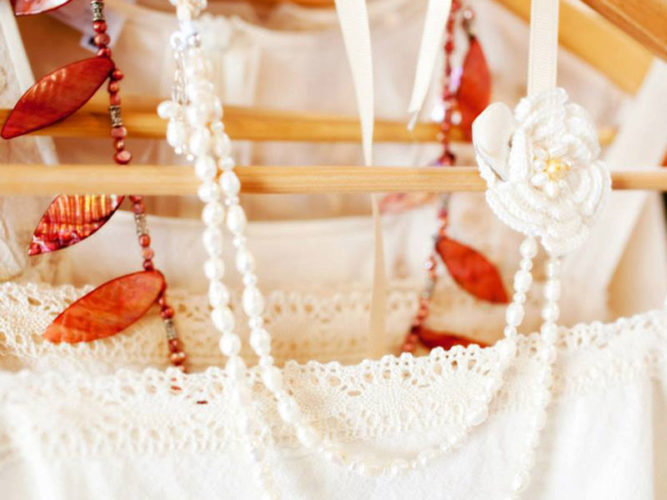 White lacy dress and white and orange beaded necklaces hanging on wooden hanger