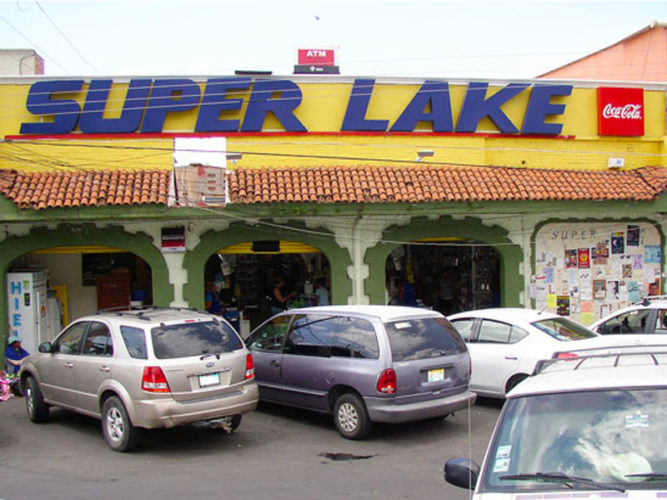 Super Lake storefront with bold blue letters, yellow walls, three open entrances to store and cars parked in front