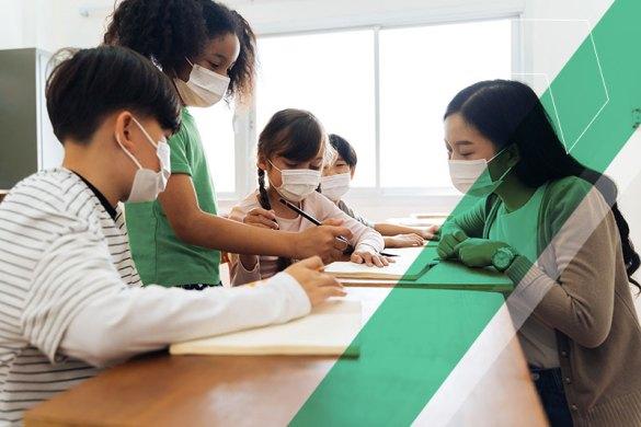 crianças usando máscara fazendo trabalho em grupo na escola