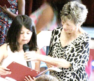 Carol Curcio helps sister of essay award winner read the winning poem .