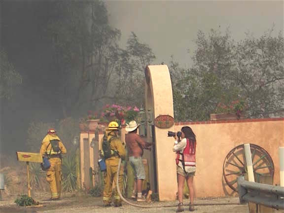 Del Dios resident Stan Smith in cowboy hat and shirtless aids Rancho Santa Fe firefighters during Witch Creek blaze.