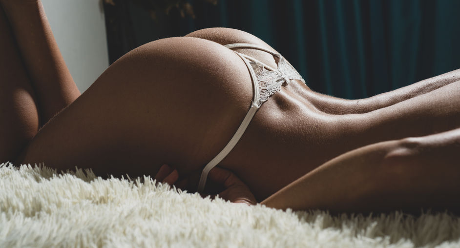 Sexy buttocks white lingerie. Attractive female ass. Erotic massage. Perfect buttocks. Waiting for you. Escort service. Desire concept. Sexy woman relaxing on fluffy bed. Female buttocks smooth skin.