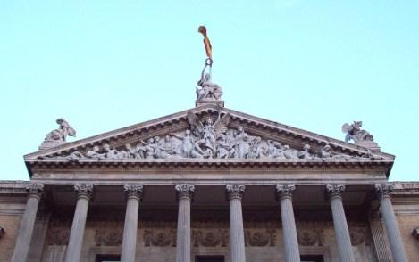 Vista parcial de la fachada de la BIBLIOTECA NACIONAL de ESPAÑA, en Madrid. El tímpano y las esculturas fueron realizadas en mármol blanco de Italia por Agustín Querol (1860-1909). La figura femenina junto al león es una personificación de España, quien, con una corona de laurel, premia simbólicamente las obras de ingenio de sus hijos. ------- Partial view of the façade of the NATIONAL LIBRARY of SPAIN, in Madrid. Tympanum and sculptures were made in Italian white marble by Agustín Querol (1860-1909). The female figure beside the lion is a personification of Spain, who, with a laurel wreath, symbolically awards the works of ingenuity of her sons.