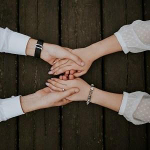 Ser generoso es clave para conseguir el éxito. las manos de un hombre sujetando las de una mujer.