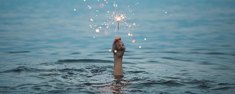 El perfeccionismo. Una mano sobresale del agua del mar sosteniendo una bengala.