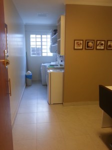 Entrada do apartamento 101, com vista pra minicozinha, sala com mesa de dois lugares e máquina de lavar.