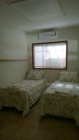 O terceiro ambiente tem mais duas camas de solteiro, além de um armário.