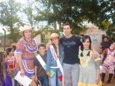 Rei e rainha caipira posando para foto com professores e direção.