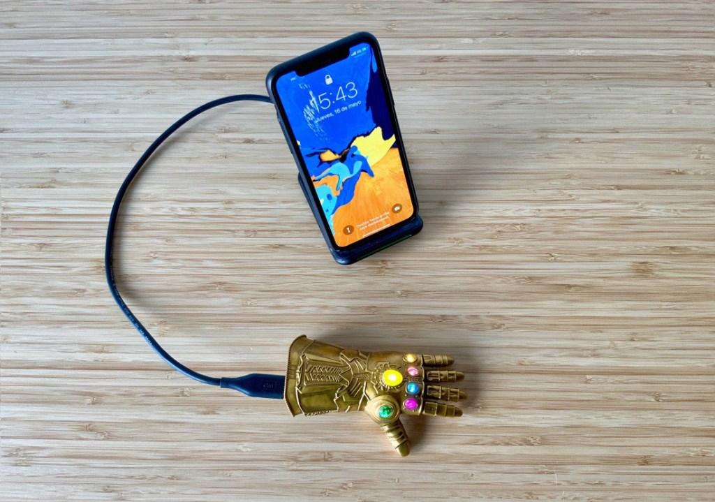 Batería externa con forma de Guantelete del Infinito sobre una mesa de madera. Cable enchufado en la base y conectado a un cargador inalámbrico con un iPhone X.