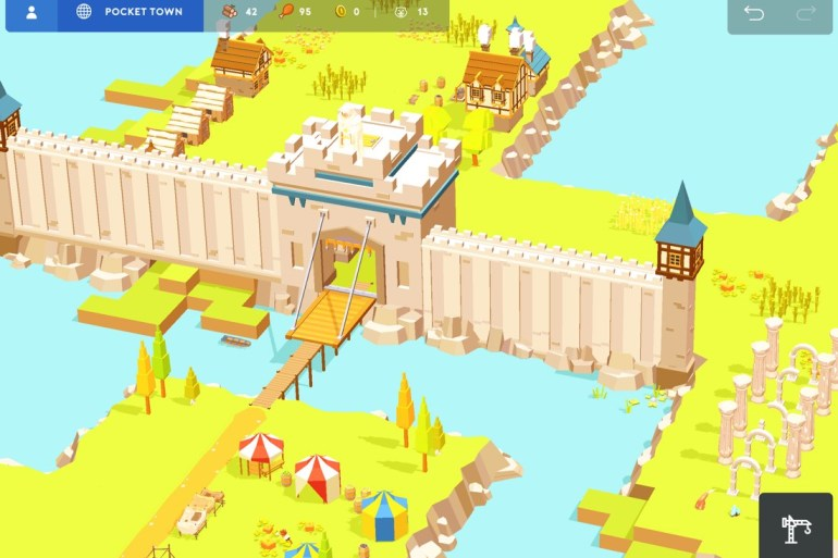 Captura de pantalla de Pocket Build. Vista de pájaro de parte del pueblo, con un campamento de tiendas de campaña y las murallas de un castillo. Escena con suelo verde y rio azul.