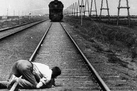 Dziga Vertov se arrodilla para filamr un tren en la pelicula Hombre con una cámara, (1929).