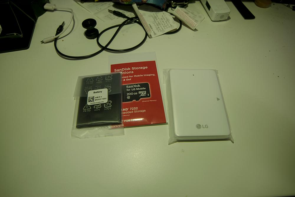 Picture of the extra battery, battery charger, and SD card from the LG Promo