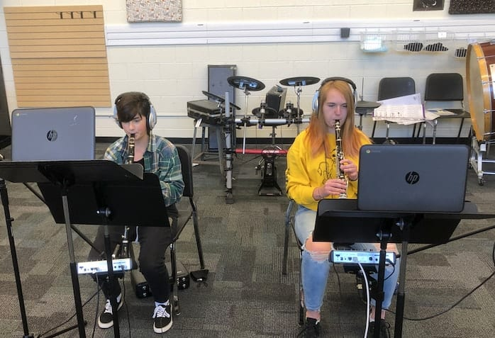 two students playing clarinet with headphones on and recording