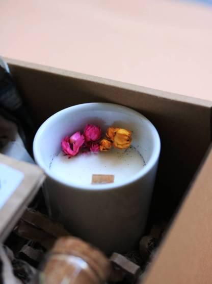 bougie dans une porcelaine blanche avec une mèche en bois, fleurs séchés rose et jaune sur le dessus, à la cire de soja