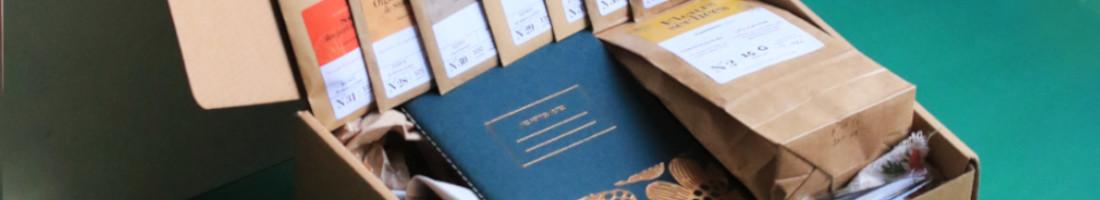 box jardinage Allemagne, échoppe végétale, sachet de graines en kraft alignés sur une boite en carton : carvi, oignon Stuttgart, souci orange des jardin, haricot blauhilde, moutarde metis, laitue feuille de chene