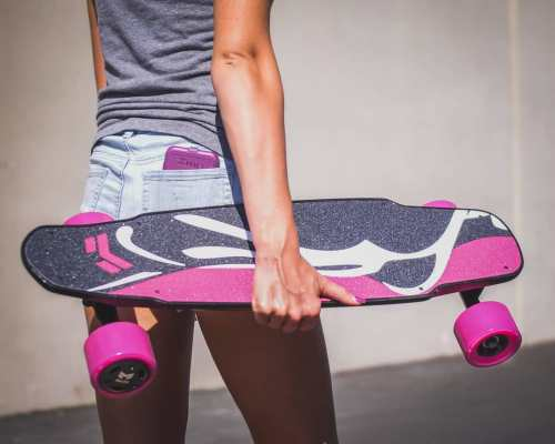 Girl Carrying Miles Electric Skateboard