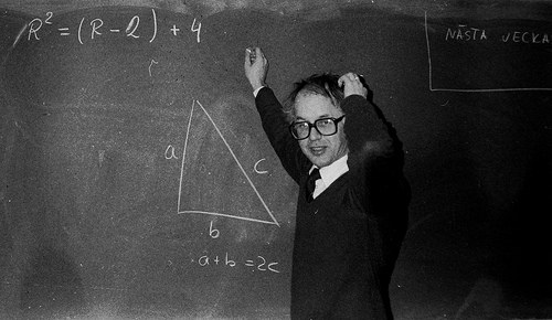 black and white image. young white student standing in front of a blackboard solving maths equation