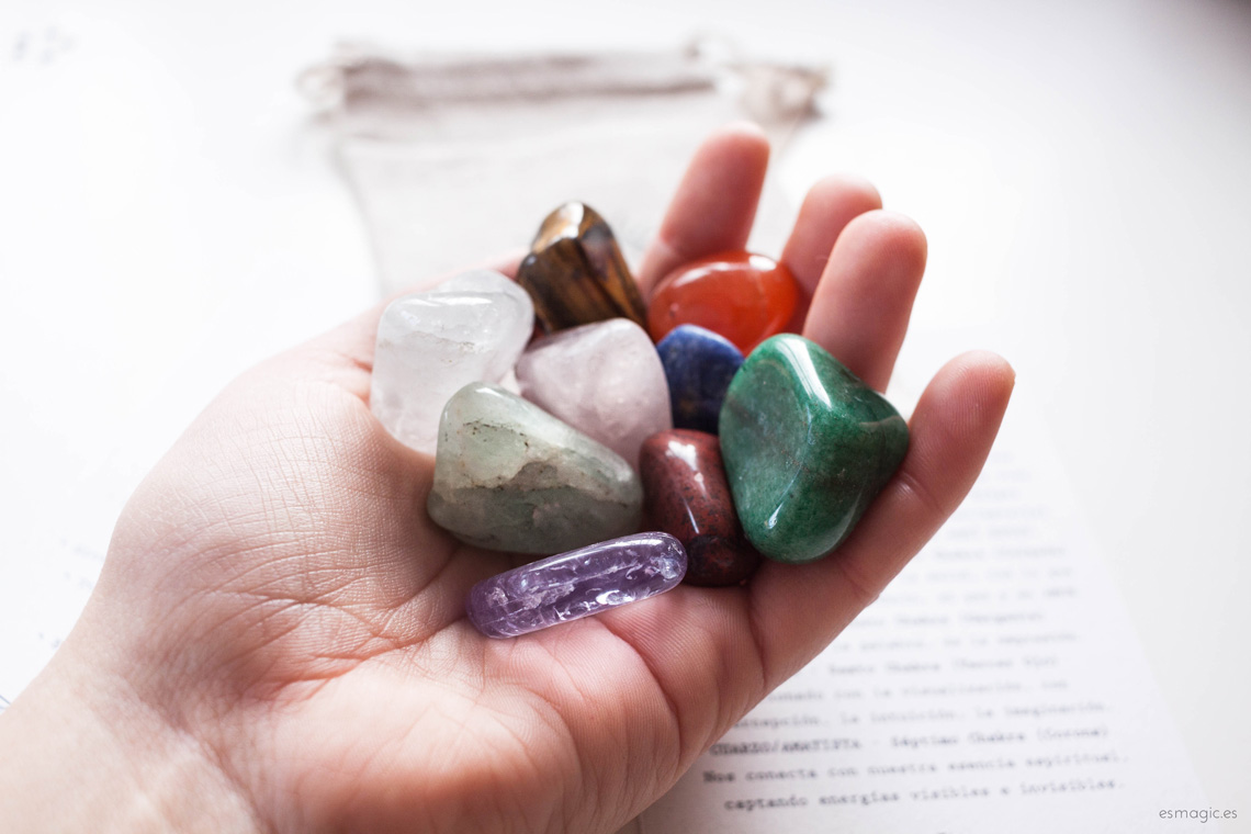 mano sujetando minerales variados, cantos rodados de los siete chakras