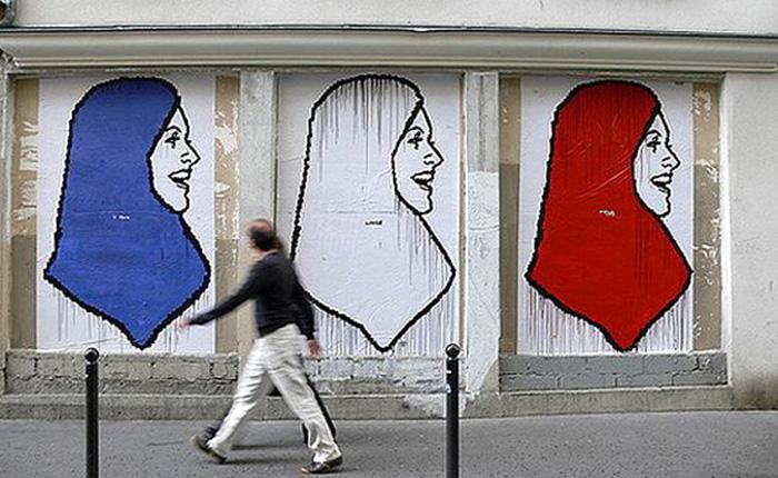 Mural en París con la imagen de tres mujeres con hiyab, cada uno de un color de la bandera francesa