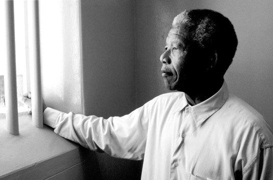 1994, Sudáfrica. Nelson Mandela mira a través de la ventana barrada de la que fue su celda durante 27 años. Imagen de © David Turnley/CORBIS