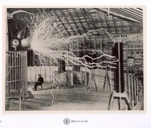 Una descarga cruza lateralmente desde el centro de la bobina a otra bobina en un soporte vertical. Tesla está sentado en su silla. Colorado Springs, 1899. © Museo de Nikola Tesla, Belgrado, Serbia