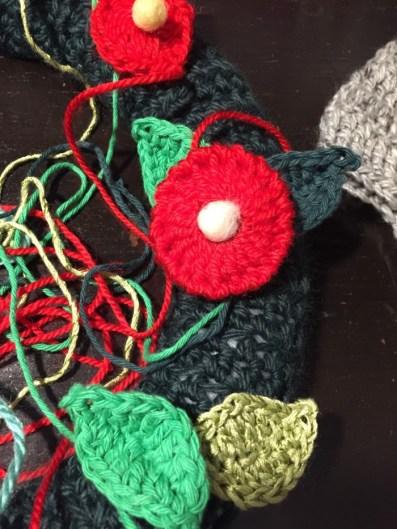 Lanas e hilos de diferentes tonos de verde, bolitas de bellón y cashmilon rojo para las flores.