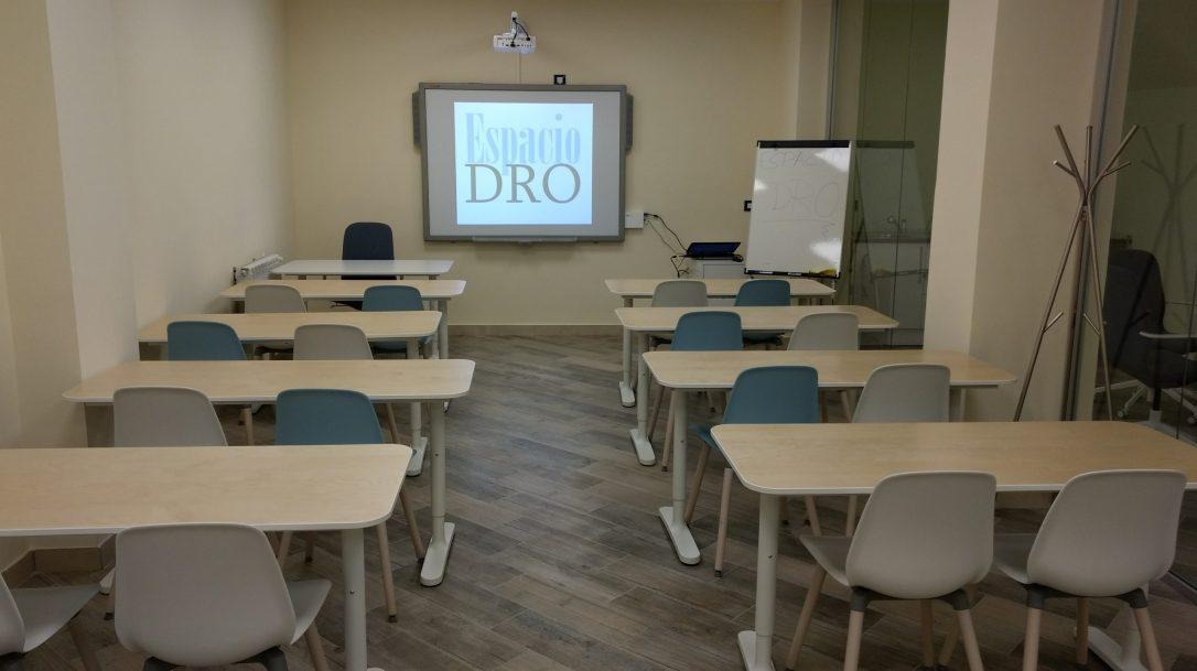 Aula de formación con proyector y mesas y sillas. Pizarra digital