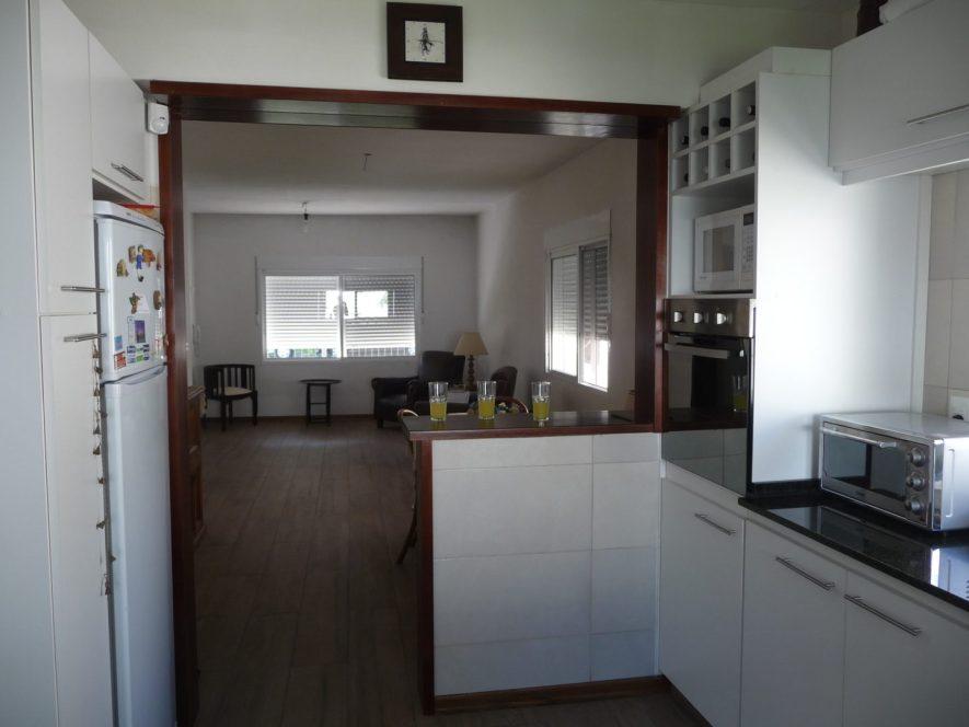 vista desde la cocina hacia la sala, barra y marcos de abertura en cedro con lustre P.U.