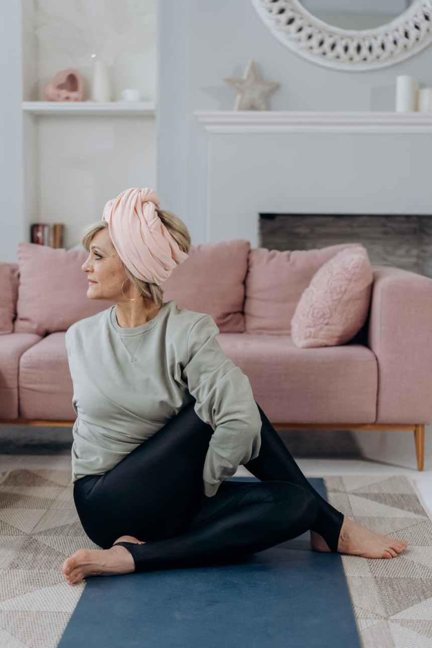 middle aged female doing half lord of the fishes in living room