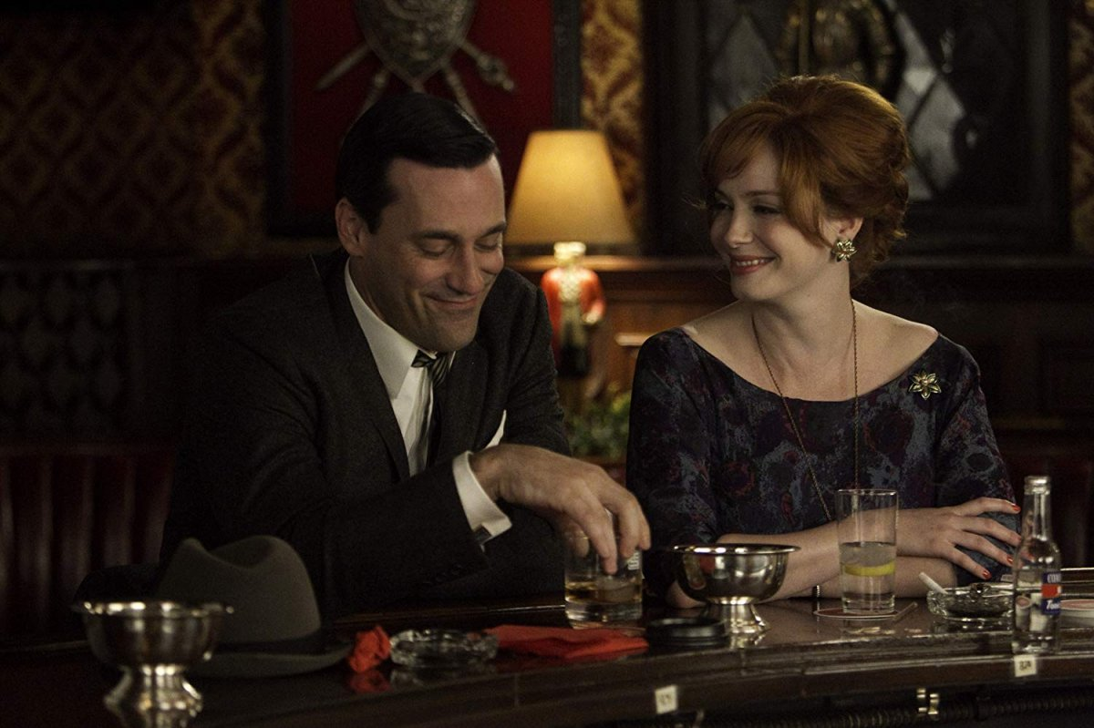 Jon Hamm (Don Draper) e Christina Hendricks (Joan Harris) em Mad Men, num bar a sorrir lado a lado