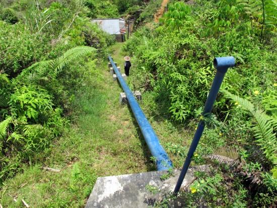 Un habitante de la aldea chequea una de las pipas del micro-generador hidroelectrico