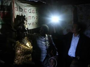 El Presidente Yoo sostiene una lámpara de energía solar que ilumina la escuela primaria en Kairobangi