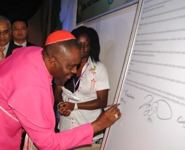 """Obispo Sunday suma su firma para la Declaración de Abuya, firmada por delegados internacionales  de mas de 20 naciones comprometiéndose a """"Crear una plataforma estratégica para promover principios universales para la construcción de paz y nuestros valores comunes como Una Familia Bajo Dios."""""""