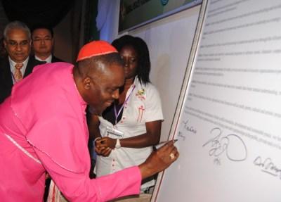"""El Obispo Sunday Onuoha suma su firma a la Declaración de Abuya en el cierre de CPLG 2013. Los delegados internacionales de más de 20 naciones se comprometen a """"Crear una plataforma estratégica para promover principios universales para la construcción de paz y nuestros valores comunes como Una Familia Bajo Dios."""""""