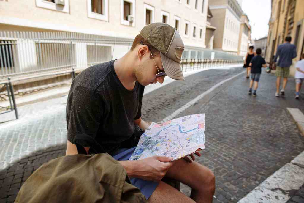 Tourist considering map of city in Rome